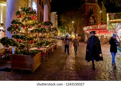 "Oldenburg, Germany - November 28, 2018: beautiful extraordinary christmas trees in front of a restaurant next to the famous Christmas market ""Lamberti Markt"", a man dressed as night watchman passes"