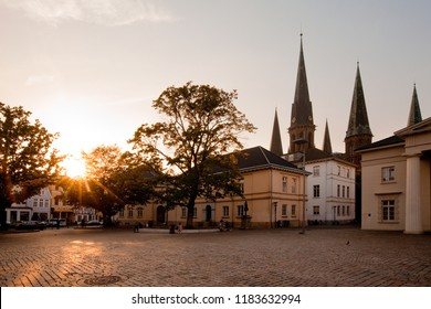 """Oldenburg, Germany - September 19, 2018: the place """"Schlossplatz"""" (castle square) with the church St. Lamberti in background while sunset on a warm and sunny summer day"""
