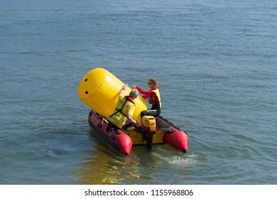 OLDENZAAL NETHERLANDS - APRIL 9, 2017: Unknown people in a small rescue boat placing a large inflatable yellow buoy