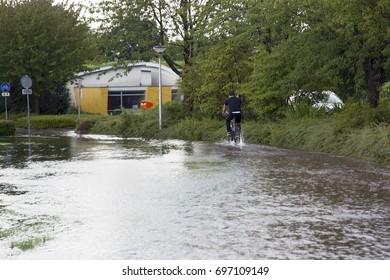 OLDENZAAL, NETHERLANDS - AUGUST 15, 2017. Men biking over brim over path after thunder storm.
