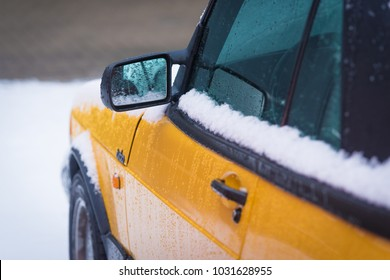 OLDENZAAL, NETHERLANDS - JANUARY 15, 2017: Detail of a yellow vintage Saab 900 turbo S convertible in snowy conditions.