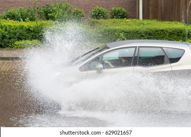 OLDENZAAL, NETHERLANDS - JULY 21, 2016: Car drives through a flooded street after heavy rain showers