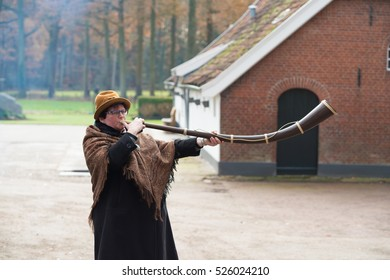 "OLDENZAAL, NETHERLANDS - NOVEMBER 27, 2016: Unknown woman blowing a so called ""midwinterhorn"", a handmade wooden instrument. It is used in the advent period in some eastern parts of the netherlands"