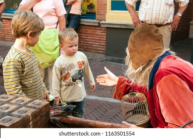 OLDENZAAL, OVERIJSSEL / NETHERLANDS - AUGUST 16 2006: Male actor asking two boys if they have seen his losing bird.