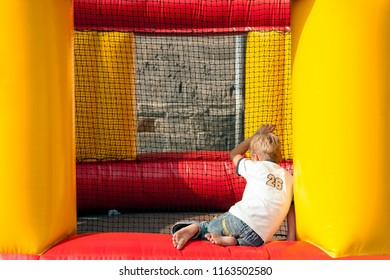 OLDENZAAL, OVERIJSSEL / NETHERLANDS - AUGUST 16 2006: Sitting boy looking at football play in blow up cage.