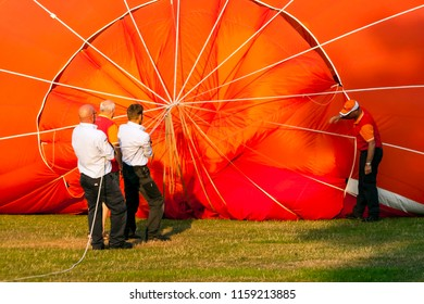 OLDENZAAL, OVERIJSSEL / NETHERLANDS - AUGUST 23 2013: Four men helping pumping air in air balloon before flying at Ballooning Festival.