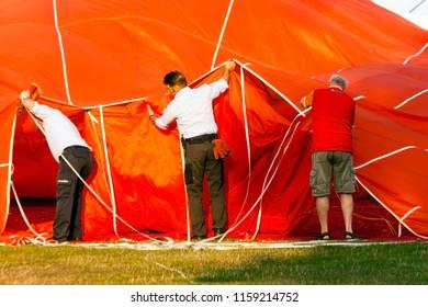 OLDENZAAL, OVERIJSSEL / NETHERLANDS - AUGUST 23 2013: Three men helping hot air balloon before flying at Ballooning Festival.