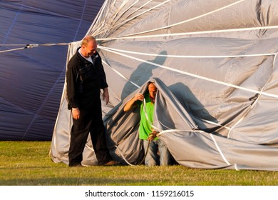 OLDENZAAL, OVERIJSSEL / NETHERLANDS - AUGUST 23 2013: Fun during pumping air in air balloon before flying at Ballooning Festival.