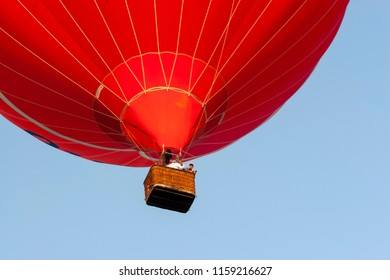 OLDENZAAL, OVERIJSSEL / NETHERLANDS - AUGUST 23 2013: Red air balloon with people flying away from Ballooning Festival.