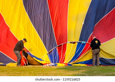 OLDENZAAL, OVERIJSSEL / NETHERLANDS - AUGUST 23 2013: Two men helping air balloon before flying at Ballooning Festival.