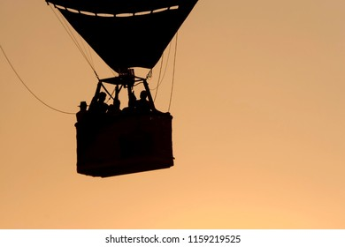 OLDENZAAL, OVERIJSSEL / NETHERLANDS - AUGUST 23 2013: Air balloon with people flying away during sunset from Ballooning Festival.