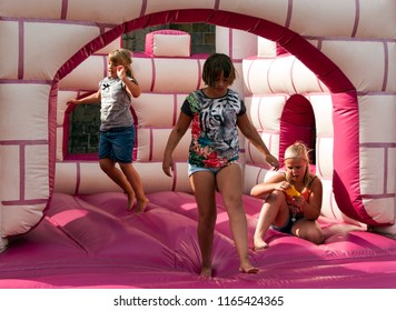 OLDENZAAL, OVERIJSSEL / NETHERLANDS - AUGUST 5 2015: Three girls playing in pink blow up castle.