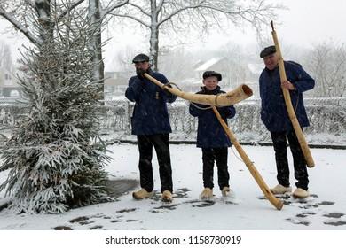 OLDENZAAL, OVERIJSSEL / NETHERLANDS – DECEMBER 12 2017: Three men with midwinterhorn next to Christmas tree during snow storm.