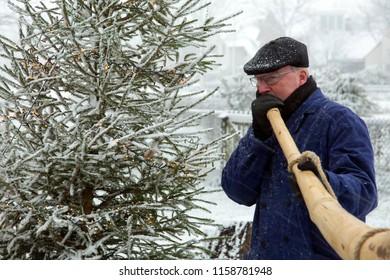 OLDENZAAL, OVERIJSSEL / NETHERLANDS – DECEMBER 12 2017: Men blowing on midwinterhorn next to Christmas tree during snow storm.