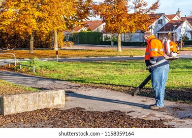 OLDENZAAL, OVERIJSSEL / NETHERLANDS - NOVEMBER 21 2013: Municipal employee blowing leaves from walking path in autumn city scape.