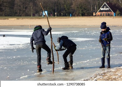 OLDENZAAL, TWENTE, OVERIJSSEL / NETHERLANDS – MARCH 2 2018: Three boys stamping with branches in ice for checking thickness