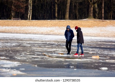 OLDENZAAL, TWENTE, OVERIJSSEL / NETHERLANDS – MARCH 2 2018: Two boys, walking on frozen lake at park Hulsbeek.