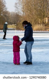 OLDENZAAL, TWENTE, OVERIJSSEL / NETHERLANDS – MARCH 2 2018: Woman learning young girl ice skating on lake at park Hulsbeek.