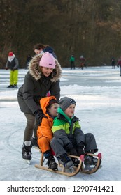 OLDENZAAL, TWENTE, OVERIJSSEL / NETHERLANDS – MARCH 2 2018: Woman pushing two boys on sledge ocer frozen lake at park Hulsbeek.