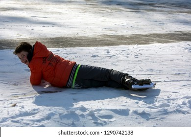 OLDENZAAL, TWENTE, OVERIJSSEL / NETHERLANDS – MARCH 2 2018: Young boy falling on ice during ice skating at park Hulsbeek.