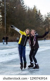 OLDENZAAL, TWENTE, OVERIJSSEL / NETHERLANDS – MARCH 2 2018: Two young girls having fun during ice skating at lake Hulsbeek.
