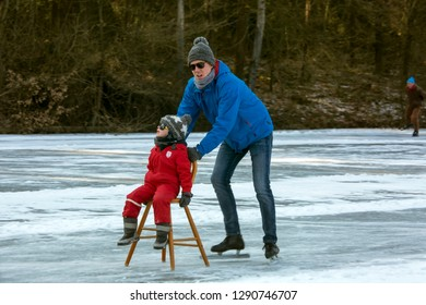 OLDENZAAL, TWENTE, OVERIJSSEL / NETHERLANDS – MARCH 2 2018: Man pushing little boy on chair over frozen lake at park Hulsbeek.
