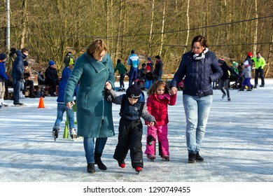 OLDENZAAL, TWENTE, OVERIJSSEL / NETHERLANDS – MARCH 2 2018: Two women learning their children ice skating at park Hulsbeek.