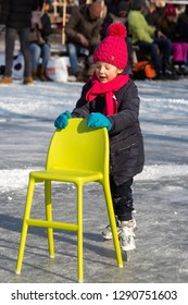 OLDENZAAL, TWENTE, OVERIJSSEL / NETHERLANDS – MARCH 2 2018: Young girl learning ice skating with a chair at park Hulsbeek.
