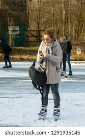 OLDENZAAL, TWENTE, OVERIJSSEL / NETHERLANDS – MARCH 2 2018: Woman busy with smartphone on ice skate ring at park Hulsbeek.
