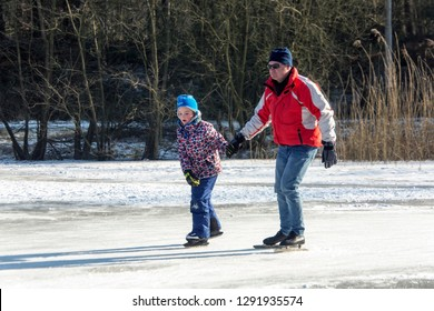 OLDENZAAL, TWENTE, OVERIJSSEL / NETHERLANDS – MARCH 2 2018: Man and an young girl skating hand-in-hand on frozen lake at park Hulsbeek.