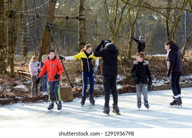 OLDENZAAL, TWENTE, OVERIJSSEL / NETHERLANDS – MARCH 2 2018: Group children talking and playing on ice skate ring at park Hulsbeek.