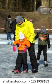 OLDENZAAL, TWENTE, OVERIJSSEL / NETHERLANDS – MARCH 2 2018: Man helping young girl with skating on ice at park Hulsbeek.