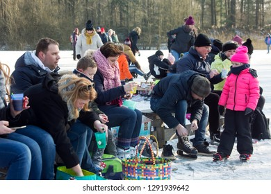 OLDENZAAL, TWENTE, OVERIJSSEL / NETHERLANDS – MARCH 2 2018: People sitting on wooden bench for putting on ice skaters and a pause.