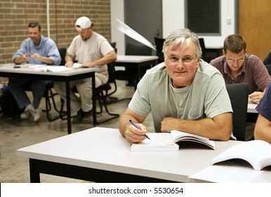 An older adult education student takes school seriously while the younger guys are goofing off making paper airplanes.