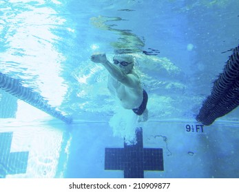 older adult man swimming laps in pool, view from underwater