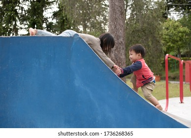 Older Asian child helping younger child up the ramp while playing at playground