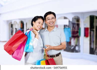 Older asian couple with shopping bags against interior of modern shopping mall