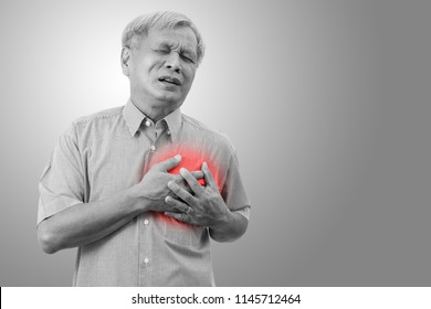 Older asian man clutching and having chest pain cause from heart attack. Heart disease in senior man with black and white isolated background. Old people healthcare insurance concept.