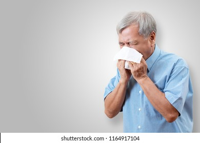Older asian man is having flu and sneezing from sickness seasonal virus problem with isolated background. Fever and cold in senior people with influenza illness and health insurance concept.