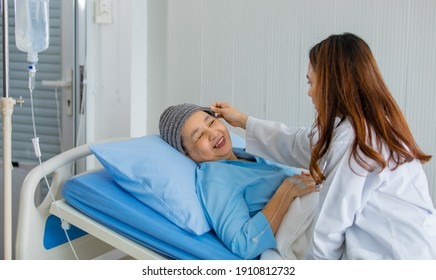 Older Asian woman patient covered the head with clothes effect from chemo treatment in cancer cure process talking to a female doctor. - Shutterstock ID 1910812732