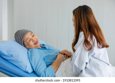 Older Asian woman patient covered the head with clothes effect from chemo treatment in cancer cure process talking to a female doctor.