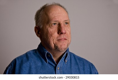 An older bald man in a blue shirt on a grey background
