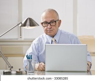 Older bald man with glasses on laptop. Desk lamp lighting from above. Horizontal.