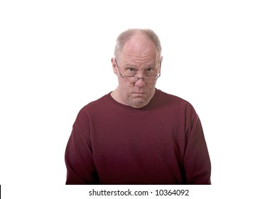 An older bald man peering over the top of reading glasses on white background
