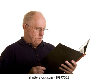 An older balding man in reading glasses reading a book