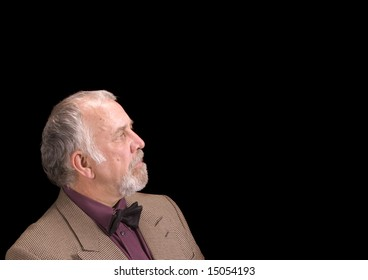older bearded businessman looking off to his left into copy space, on his left, isolated over black