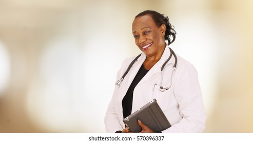 An older black doctor posing for a portrait in her office