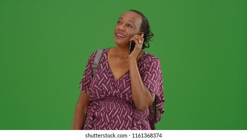 A older black woman taking a mobile phone call on green screen