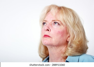 Older blond haired woman looking upward with a solemn expression.  Model is isolated on a white background and there is ample copy space.