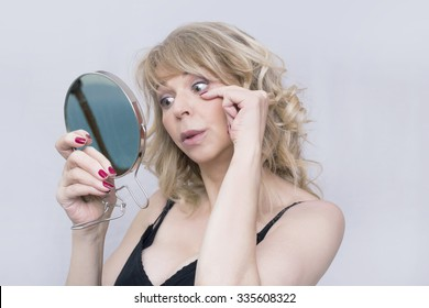 Older blonde woman checking on her wrinkles in a mirror